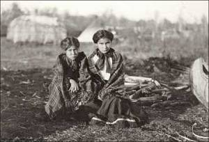 Ojibwa Girls with Longhouse in the Background (location unknown)